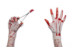 Surgery and medicine theme: doctor bloody hand in glove holding a bloody surgical clamp with swab and performs surgery Stock Image