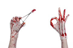 Surgery and medicine theme: doctor bloody hand in glove holding a bloody surgical clamp with swab and performs surgery Royalty Free Stock Image