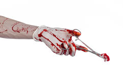 Surgery and medicine theme: doctor bloody hand in glove holding a bloody surgical clamp with swab and performs surgery Royalty Free Stock Photography