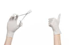Surgery and medicine theme: doctor's hand in a white glove holding a surgical clamp with swab isolated on white background Royalty Free Stock Image