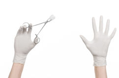 Surgery and medicine theme: doctor's hand in a white glove holding a surgical clamp with swab isolated on white background Stock Photography