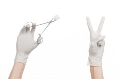 Surgery and medicine theme: doctor's hand in a white glove holding a surgical clamp with swab isolated on white background Stock Photo