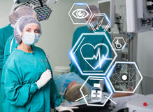Surgery team with futuristic healthcare icons stock photography