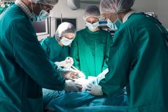 Surgery. Team operating in a surgical room Stock Image