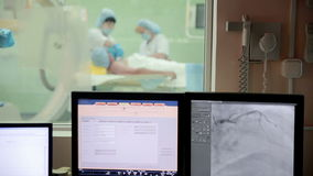 Surgery. Unrecognizable doctor controls operation performing in hospital operating room on computer screens. Unrecognizable doctor controls operation performing stock video footage