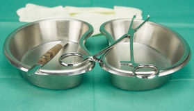 Surgical clamp and knife placed on kidney shape bowl Royalty Free Stock Images