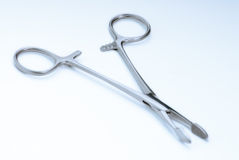 Surgical clamps. On a soft blue background surgical blue Stock Photos