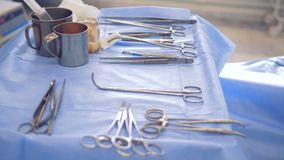 Surgical instruments are lying on a hospital table which is covered with protective material. 4K stock footage