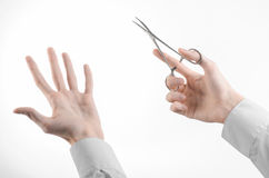 Surgical and Medical theme: doctor's hand in a white lab coat holding a surgical clamp scissors isolated on a white background. In studio Stock Image