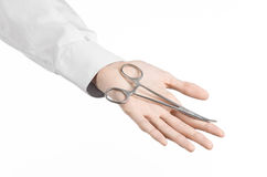 Surgical and Medical theme: doctor's hand in a white lab coat holding a surgical clamp scissors isolated on a white background Stock Images