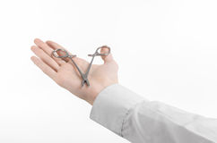 Surgical and Medical theme: doctor's hand in a white lab coat holding a surgical clamp scissors isolated on a white background. In studio Royalty Free Stock Photo