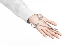 Surgical and Medical theme: doctor's hand in a white lab coat holding a surgical clamp scissors isolated on a white background Stock Photo