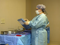 Surgical preparations. Scrub nurse preparing supplies for surgery Royalty Free Stock Images