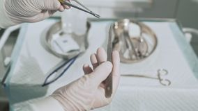 Surgical table with sterile medical instruments. The assistant gives the surgeon the scalpel blade. Closeup shot of. Doctors hands with surgical supplies stock video footage