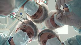 Surgical team bends over the patient stock photos