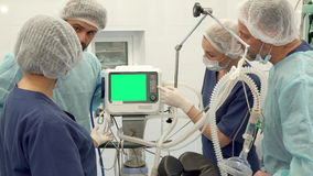 Surgical team discussing something on monitor. Surgical team of four members discussing something on monitor. Two bearded surgeons and two nurses looking at stock footage