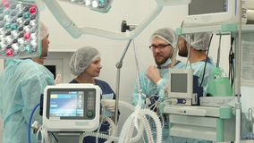 Surgical team talking at the surgery room. Three surgeons and two nurses standing on background of modern medical equipment. Long shot of young bearded medical Stock Image