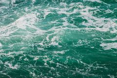 The surging sea water background. Texture. The surging sea water background. Storm. Water with foam. Texture royalty free stock photo