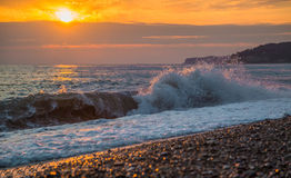 The surging waves on the beach at sunset Stock Photography