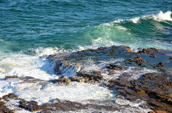 Surging waves over a tessellated rock platform weathered by ocean waves. On the New South Wales coast, Australia Stock Image