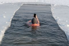 A lover of winter swimming in a pit on the ice photographs himself on the phone. Opening of the winter swimming season. stock photo