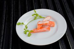 Surimi. On a black plate decorated with parsley Stock Photography