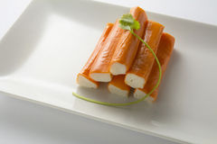 Surimi or crab sticks in a white rectangular plate. . White back Stock Photography