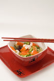 Surimi salad. Surimi salad in a red bowl. Selective focus. White background Royalty Free Stock Photos