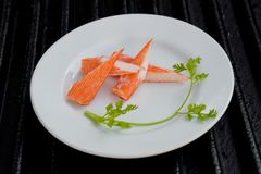 Surimi. On a black plate decorated with parsley Royalty Free Stock Photos