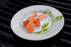 Surimi. On a black plate decorated with parsley Stock Image
