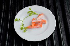 Surimi. On a black plate decorated with parsley Royalty Free Stock Photo