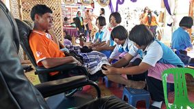 Asian student group is massaging to their foot customer. SURIN, THAILAND – JULY 10, 2018:  Asian student group is massaging to their foot customer,  the Royalty Free Stock Photo