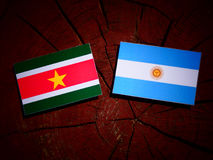 Suriname flag with Argentinian flag on a tree stump  Royalty Free Stock Images