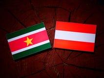 Suriname flag with Austrian flag on a tree stump  Stock Photo
