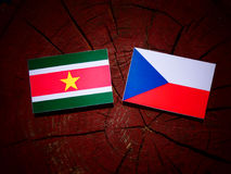Suriname flag with Czech flag on a tree stump  Royalty Free Stock Photo