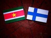 Suriname flag with Finnish flag on a tree stump isolated Stock Photos
