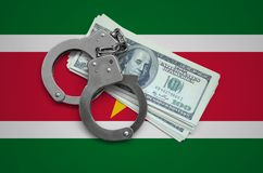 Suriname flag with handcuffs and a bundle of dollars. Currency corruption in the country. Financial crimes royalty free stock photography