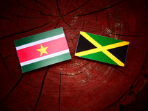 Suriname flag with Jamaican flag on a tree stump  Stock Photo
