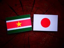 Suriname flag with Japanese flag on a tree stump isolated Royalty Free Stock Photo