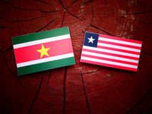 Suriname flag with Liberian flag on a tree stump isolated Royalty Free Stock Photography