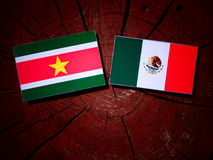 Suriname flag with Mexican flag on a tree stump isolated Royalty Free Stock Photo