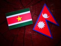 Suriname flag with Nepali flag on a tree stump isolated Royalty Free Stock Photography
