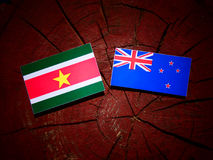 Suriname flag with New Zealand flag on a tree stump isolated Stock Photo
