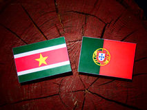 Suriname flag with Portuguese flag on a tree stump isolated Stock Photos