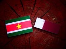 Suriname flag with Qatari flag on a tree stump isolated Stock Photography