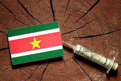 Suriname flag on a stump with syringe injecting money Stock Images