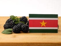 Suriname flag on a wooden panel with blackberries isolated on a Stock Image