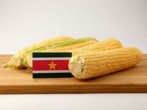 Suriname flag on a wooden panel with corn isolated on a white ba Stock Photos