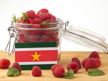 Suriname flag on a wooden panel with raspberries isolated on a w Stock Image