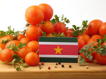Suriname flag on a wooden panel with tomatoes isolated on a whit Stock Photo